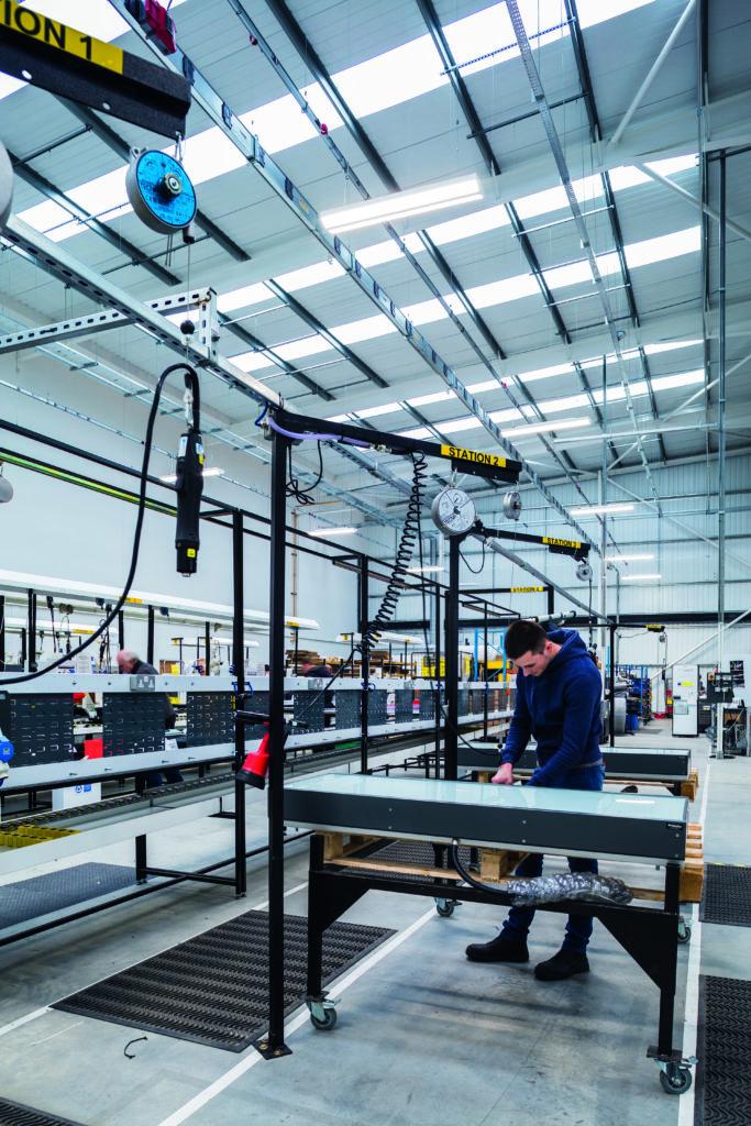 Factory worker making light box for cross rail
